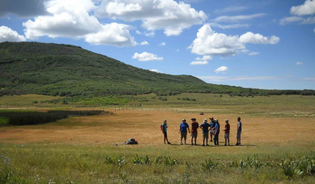 A group of students stand in a field.