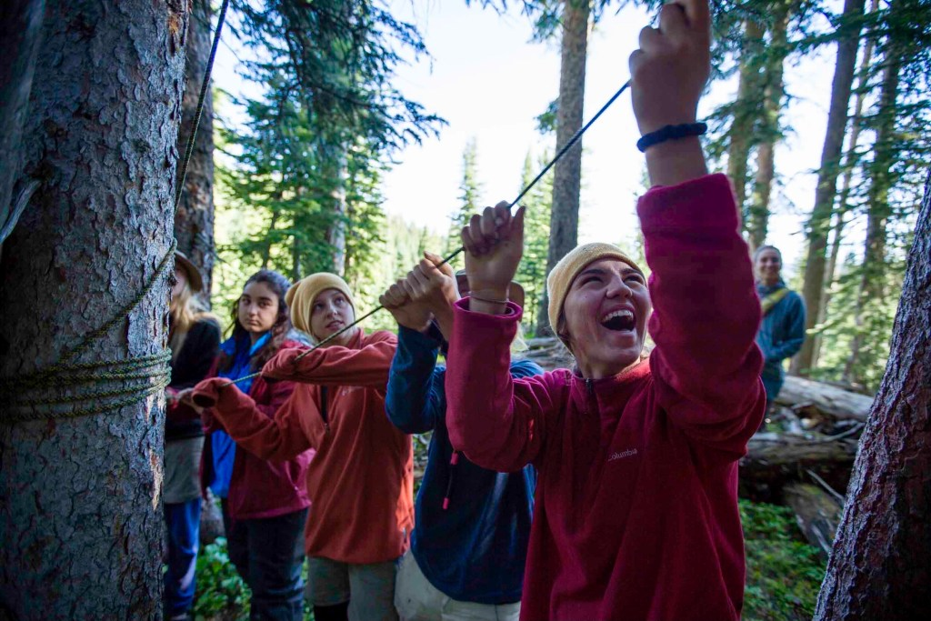 A group of adolescent students at Open Sky Wilderness Therapy smile as they work together to set up a bear hang.