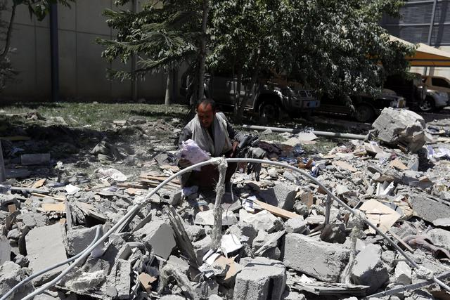 epa04741293 A gunman loyal to former Yemeni President Ali Abdullah Saleh, searches amid the rubble of Saleh's residence following an airstrike carried out by the Saudi-led alliance in Sanaa, Yemen, 10 May 2015. According to reports, the Saudi-led coalitions warplanes bombed the residence od Saleh, who is accused of supporting the Houthis, as well as on the province of Saada, even as the Houthis accept a five day humanitarian ceasefire due to begin 12 May.  EPA/YAHYA ARHAB
