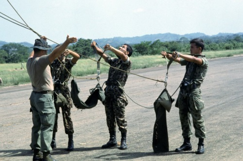 Army special forces soldier instructing columbian parachuters