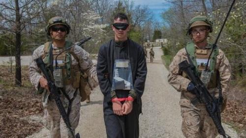 marine military police escort a mock prisoner