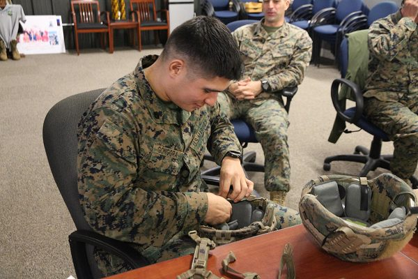 0300 MOS Staff Sergeant evaluates a helmet retention system