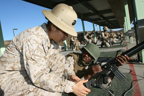 combat marksmanship coach helps a Marine find his settings for teh USMC rifle qualification