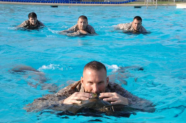 Marines use their packs as floatation devices during USMC swim qual