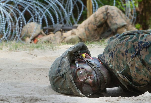 Marine recruit crawling through the sand during the crucible at Parris Island