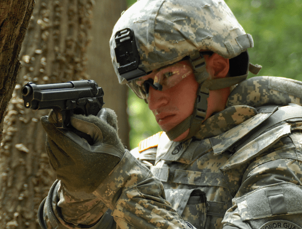 A United States Army soldier in 2009 demonstrates the usage of his Beretta M9 sidearm.