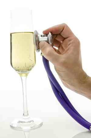Alcohol withdrawal and dependency diagnostic; Male hand holding a stethoscope on a glass of wine.Concept of consequences of drinking alcohol.