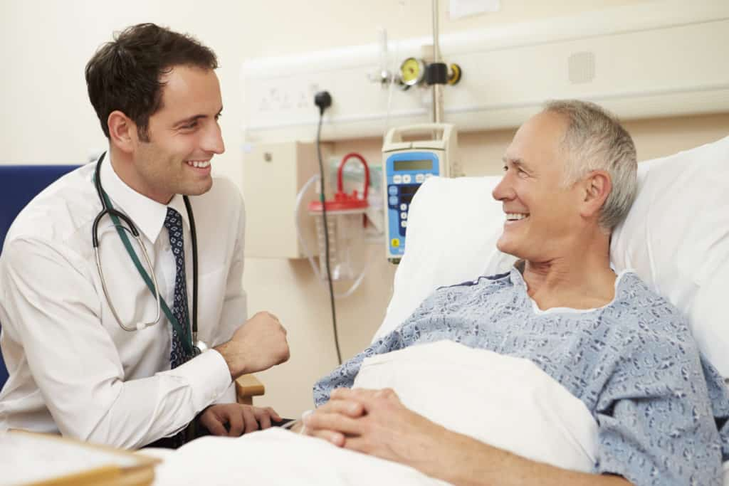 happy male patient receiving medical detox for alcohol dependence from a medical detox doctor in a hospital bed
