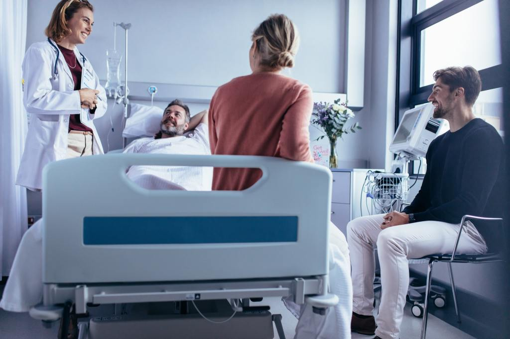 man in hospital bed surrounded by doctor and family after successfully completing medical detox for opioids