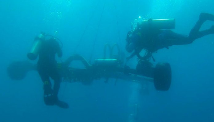 Experts working underwater to lay optical fibre cable on the seafloor
