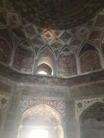 No stone grills characteristic of Mughal architecture. Sunlight seeps through the window of the double domed structure.