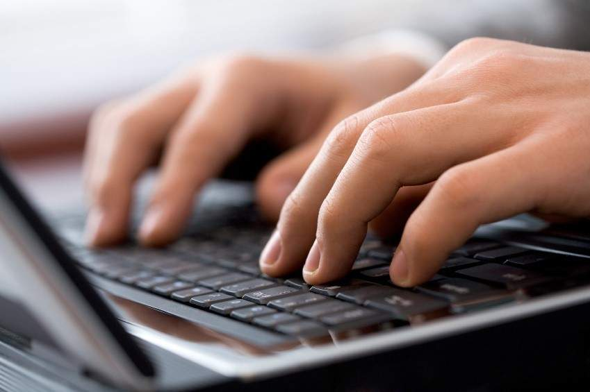 hacker or business person types on a keyboard
