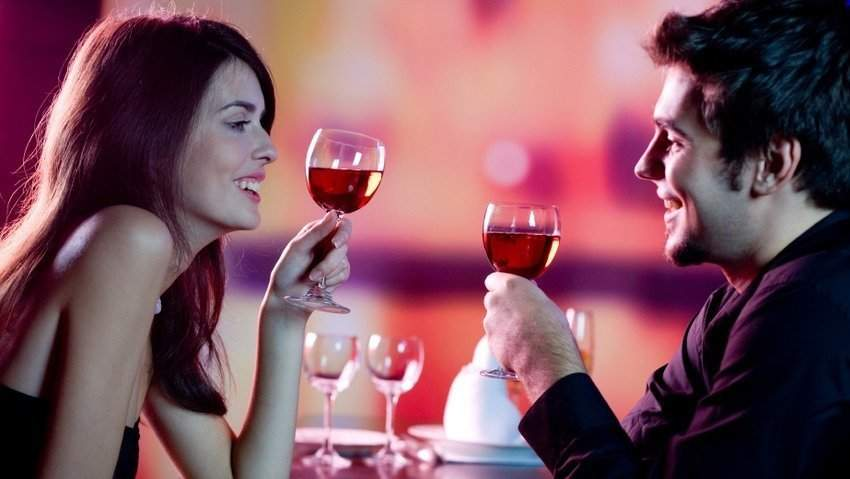 couple drinks dine wine and toasts and is happy