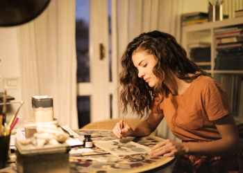 young woman painting on paper at workplace
