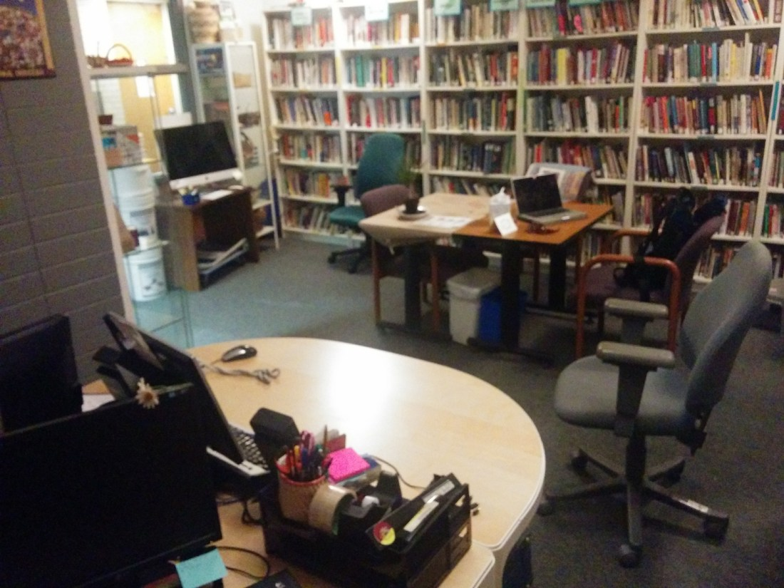 Interior view of our resource centre showing tables, an iMac computer and a wall of books on shelves
