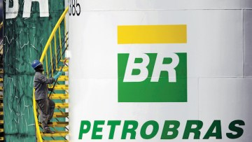 A worker paints a tank of Brazil's state-run Petrobras oil company in Brasilia