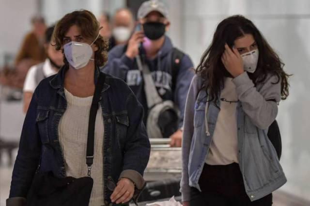 Passageiros que usam máscaras como medida de precaução para evitar a contração do novo coronavírus, COVID-19, chegam em um voo da Itália no Aeroporto Internacional de Guarulhos.