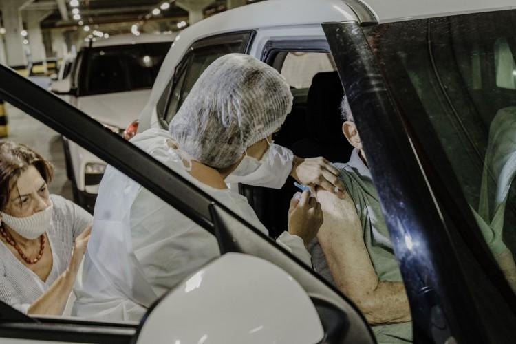 Vacinação de idosos no Centro de Eventos em Fortaleza sendo registrada por familiar. No país, casos de não aplicação foram registradas em seis municípios, nenhum no Ceará até o momento (Foto: JÚLIO CAESAR)
