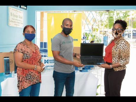 Travis Graham (centre), executive director, Oracabessa Foundation, hands over two laptops to Natricia Lothian (right), principal, Oracabessa Primary and High School. NCB Foundation has partnered with Oracabessa Foundation to assist its COVID-19 Education Support Initiative to provide the Oracabessa Primary and High School with two brand new laptops, along with printing supplies. The donations of the laptops, printer ink and paper has helped the school to serve its student population better. Looking on is Brenda Angus, board member, Oracabessa Foundation.