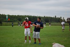 Coach Andres Perez, talks to quarterback Quinten Poteralski about plays the team will be learning at practice. Perez continues to coach the team on when they will next face off against Freedom on October 24th.