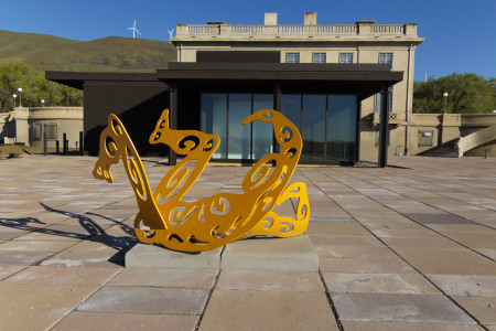 """Plaza, Mary and Bruce Stevenson Wing, with original museum building behind. On the hills are some of the windmills that help support Maryhill financially. Foreground: Alisa Looney (Portland, Ore.), """"Roll & Play,"""" 2007, powder-coated and flame cut mild steel, 36"""" x 75"""" x 48"""". Gift of the North Star Foundation, 2008.06.001. Photography Scott Thompson"""