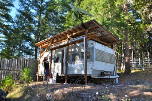 "Renee Couture looks up at her artist studio ""trailer"" situated on acreage in the central Southern Oregon region./Sabina Poole"