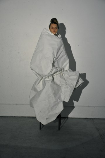 Artist Blair Saxon-Hill, wrapped in paper, tied in rope on a pedestal, and lit in the bright glare of a 1980s projector. Photo: Sabina Poole