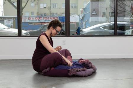 Photograph of artist performing in gallery, sitting on floor, emerging from cushioned fabric sculpture made of light and dark purple fabrics and yarn that match the artist's dress.