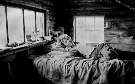 Black and white photograph of a young woman with cropped blonde hair and simple, outdoorsy clothes, reclining on a slightly messy bed inside a small log cabin with two paned windows behind her.