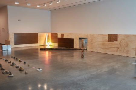 Gallery installation featuring low plywood façade wrapping around corner of two walls, and on the floor two yellow fluorescent lights, two logs, a mirror, a silver box, and an assortment of small objects arranged in a grid.