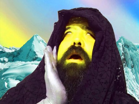 Photo of bearded man with yellow-painted face and purple lace shroud over head, holding hand to cheek and looking upwards with mouth open and eyes rolled back as if in agony or ecstasy. alpine scene in background