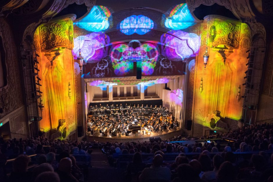 Image of the Arlene Schnitzer Concert Hall during performance, symphony plays onstage while colorful animations are projected on theater facade surrounding musicians