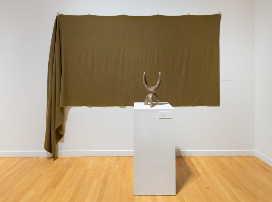 View of a gallery wall with a bolt of moss-green woven wool fabric hanging from clips, one side is draping down to the floor. In front, on a white pedestal, is a small beige ceramic sculpture that has a tripod-like base and a crescent-moon shaped upper that resembles animal horns.