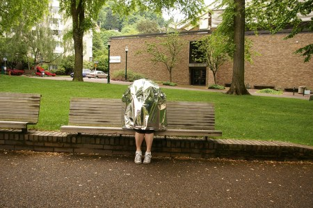 A photo of a person sitting on a park bench on the Portland State University campus, covered from head to knee in reflective silver mylar, their sneaker-clad feet and bare shins sticking out of the bottom.