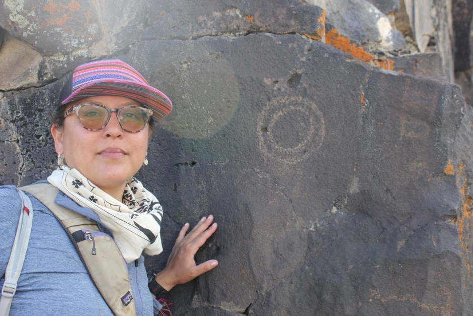 Ka'ila Farrell Smith leans against a rock face bearing a circular petroglyph, she wears a pale blue t-shirt, white patterned bandana around her neck, brown tinted sunglasses and a multicolored baseball cap.
