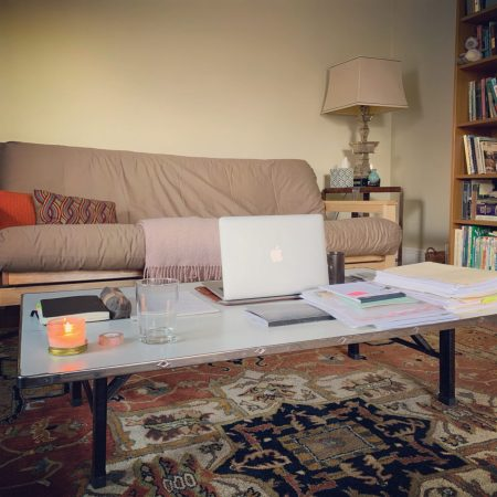A living room featuring a couch and decor in neutral colors, with a laptop and some notebooks laid out on the coffee table, which has been turned into a makeshift home office