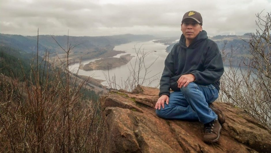 Image of Greg Archuleta sitting on a rocky outcropping above a river.