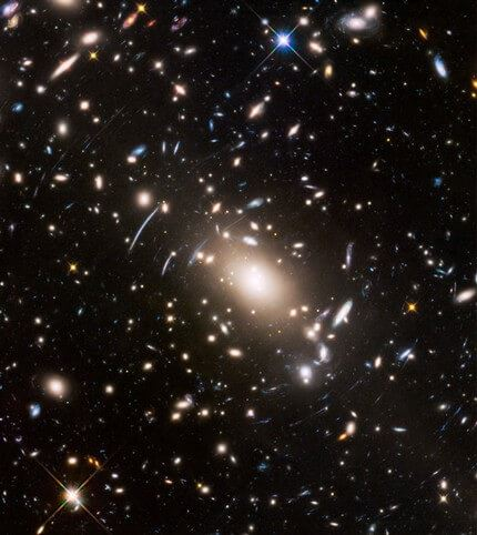 Abell S1063, a galaxy cluster, was observed by the NASA/ESA Hubble Space Telescope as part of the Frontier Fields programme. The huge mass of the cluster acts as a cosmic magnifying glass and enlarges even more distant galaxies, so they become bright enough for Hubble to see.