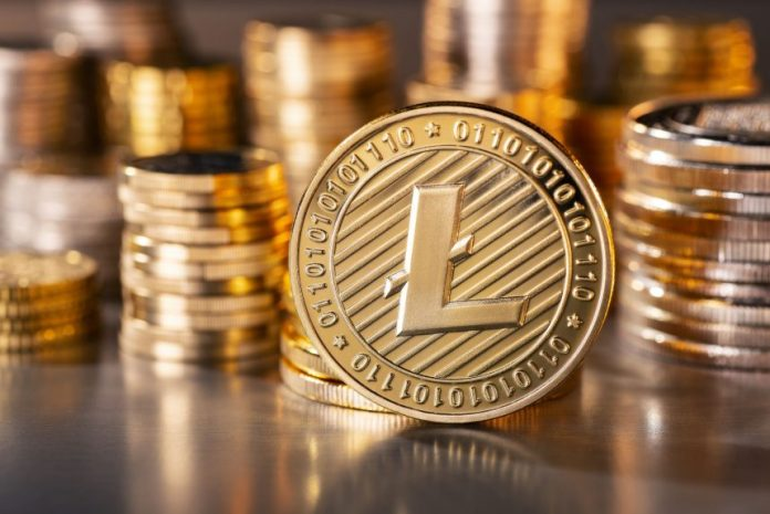 Picture of a gold Litecoin standing in front of stacks of other gold Litecoins