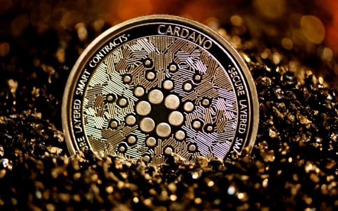 Picture of a gold and black Cardano coin half-sunk into the sand
