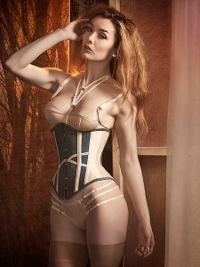 Miss Miranda wears an ivory and green silk corset and ivory silk lingerie.