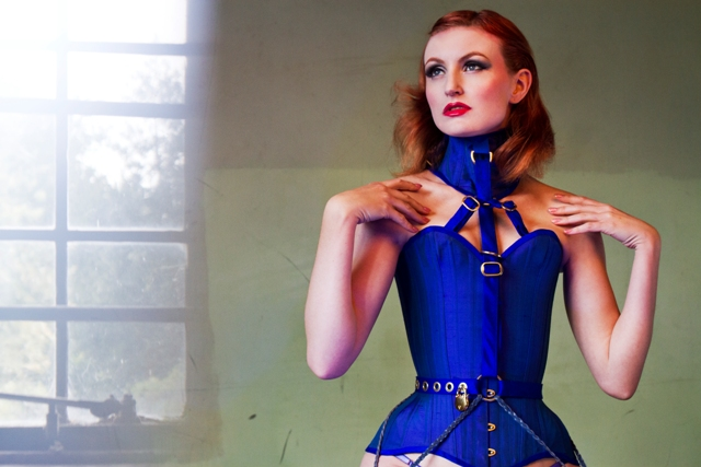 Close up of model wearing blue silk overbust corset with locking belt and posture collar.