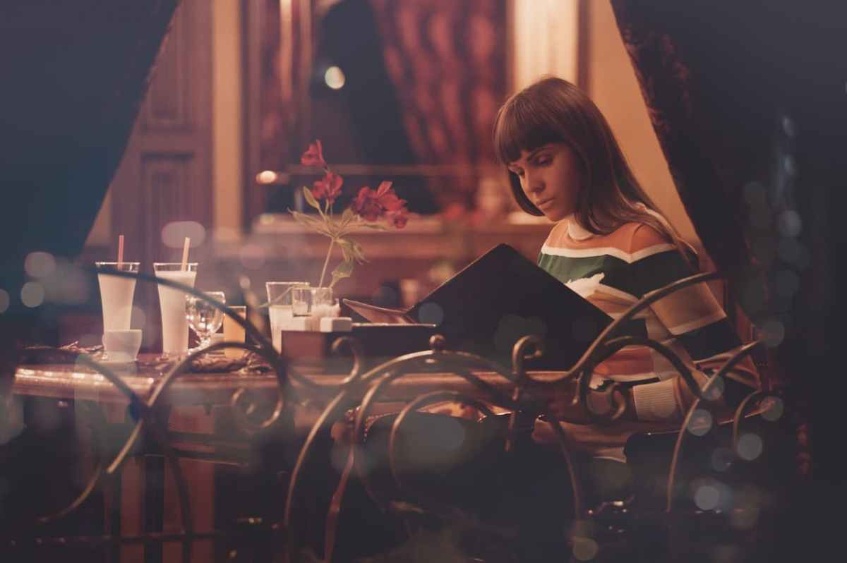Frau im Restaurant mit Speisekarte in der Hand
