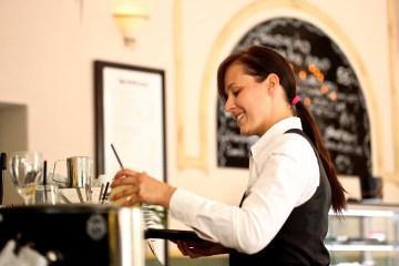 Freundliche Kellnerin an der Kaffeemaschine