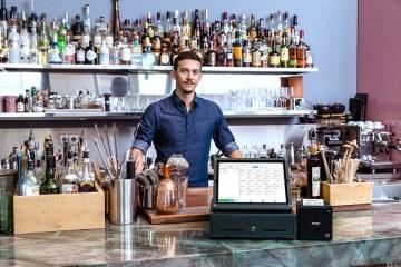 Ein Gastronom hinter seiner Bar, vor ihm das Kassensystem von orderbird