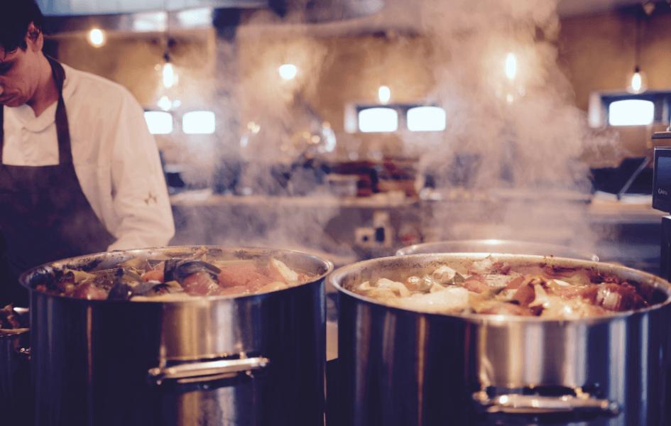 Koch hinter zwei großen Töpfen in einer professionellen Küche