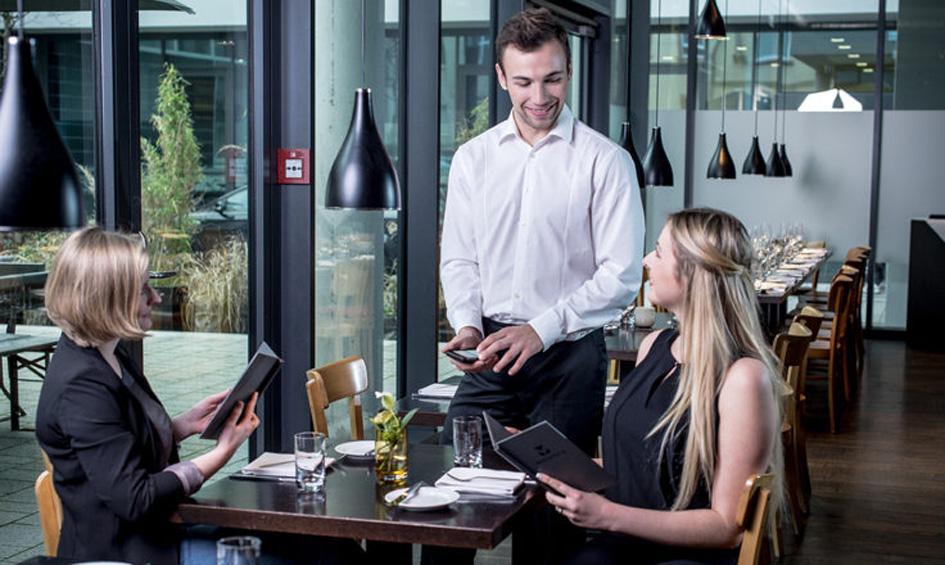Ein Kellner nutzt Funkbonieren, um eine Bestellung zweier weiblicher Gäste aufzunehmen