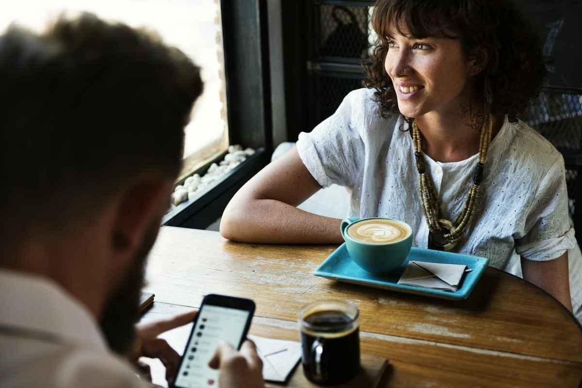 Pärchen im Café, er ist auf Facebook, sie trinkt Kaffee