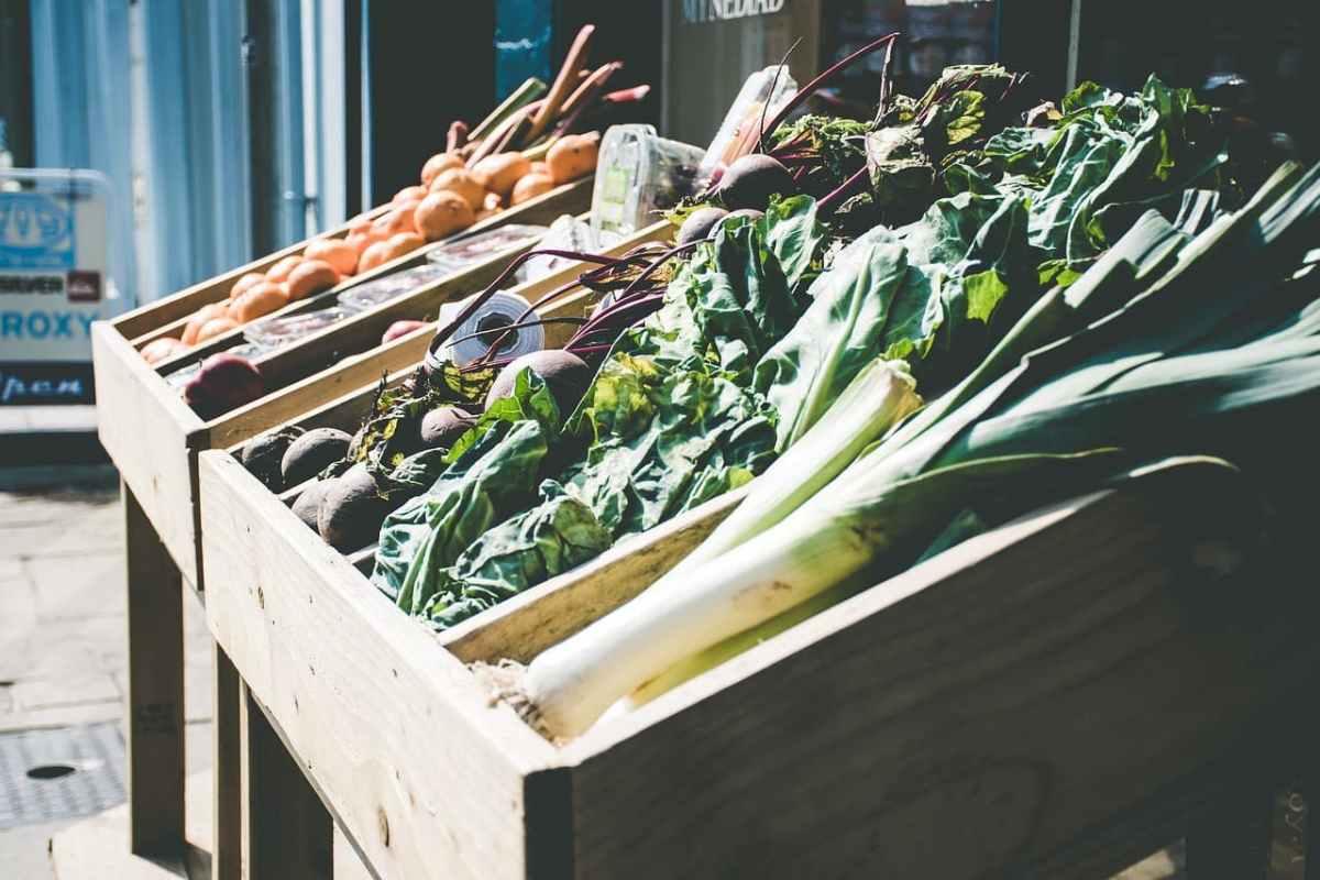 Gemüse, dass in Holzkisten auf dem Markt verkauft wird