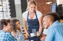 Eine lachende Kellnerin bedient eine Gastgruppe, für die Gästebindung in der Gastronomie setzt sie auf Freundlichkeit